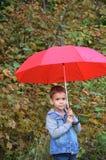 有棕色眼睛的英俊的逗人喜爱的男孩在一件牛仔裤夹克在有一把红色伞的秋天公园, 免版税图库摄影