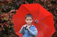 有棕色眼睛的英俊的逗人喜爱的男孩在一件牛仔裤夹克在有一把红色伞的秋天公园, 库存图片