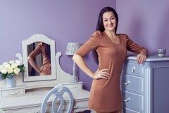 有棕色礼服和长的黑发的美丽的妇女在她的在她的摆在党面前的梳妆台附近的屋子里 免版税库存照片