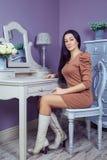 有棕色礼服和长的黑发的美丽的妇女在她的在她的摆在党面前的梳妆台附近的屋子里 免版税库存图片