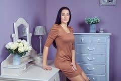 有棕色礼服和长的黑发的美丽的妇女在她的在她的摆在党面前的梳妆台附近的屋子里 库存图片