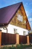 有棕色篱芭的白色乡间别墅由在一个现代样式与砖专栏,乡间别墅的设计的polyprofil制成 免版税库存照片