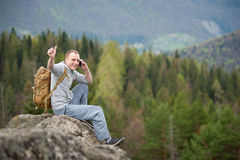 有棕色背包的男性登山人在岩石峰顶  图库摄影