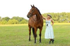 有棕色马的农夫妇女在牧场地 库存照片