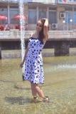 有棕色头发、一张好的面孔和摆在一个好的图的美丽的妇女在喷泉的背景 免版税库存照片