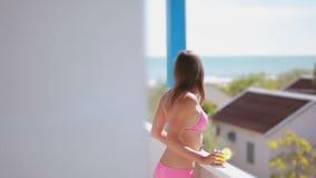 有棕色头发的女孩享受海视图的,当站立在手段的阳台时 影视素材
