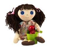 有棕色头发的布洋娃娃女孩在绿色桶附近用红色苹果 库存照片