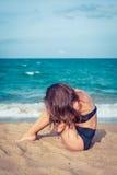 有棕褐色的皮肤的性感的妇女在黑泳装坐海滩的沙子 女性在膝盖上把她的头放在海附近 库存照片