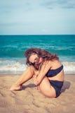 有棕褐色的皮肤的性感的妇女在黑泳装坐海滩的沙子 女性在膝盖和胳膊上把她的头放 库存照片