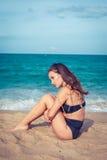 有棕褐色的皮肤的美丽的性感的妇女在黑泳装坐海滩的沙子 女性拥抱她的膝盖临近海 库存图片