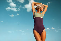 有棕褐色的美丽的性感的妇女在反对天空的泳装 免版税库存照片