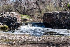 有森林和石头的老使命水坝 库存图片