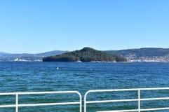 有森林的海岛海湾的 绿松石和清楚的水,从海滩散步的看法有白色扶手栏杆的 好日子、蓝色和gree 免版税库存照片