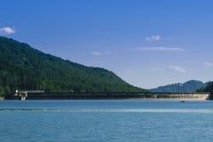 有森林的湖水坝在背景中 库存照片