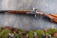 有森林静物画的老古色古香的长的枪在灰色背景,历史武器 库存图片