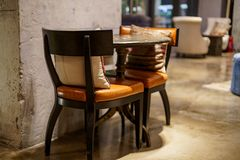 有椅子、桌和坐垫的艺术内部地方室内在与灰色的都市葡萄酒咖啡馆抓了墙壁 免版税库存照片