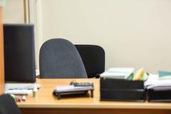 有椅子和个人计算机显示器的空的工作地点桌的 免版税库存照片