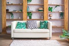 有植物、白色沙发和时髦的家具的舒适轻的室在斯堪的纳维亚样式 客厅内部概念 选择聚焦 免版税库存照片