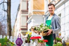 有植物供应的卖花人在商店 库存图片