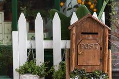 有植物和白色篱芭的木信箱 免版税图库摄影