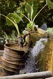 有植物和装饰小瀑布喷泉的泥罐在希腊村庄Argiroupoli,克利特,希腊 免版税库存图片