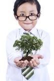 有植物的小男孩在手上 免版税图库摄影
