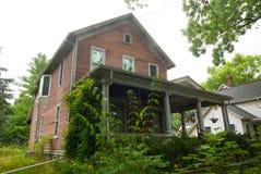 有植物的老木材房子前景的 免版税库存图片