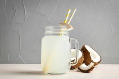 有椰子水和新鲜的坚果的金属螺盖玻璃瓶 库存图片