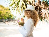 有椰子鸡尾酒的典雅的卷曲妇女在海滩 库存照片