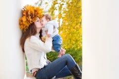 有槭树叶子的母亲缠绕亲吻她的婴孩 免版税图库摄影