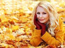 有槭树叶子的秋天妇女 秋天的白肤金发的美丽的女孩 库存照片