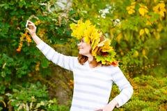 有槭树的愉快的妇女留下做selfie的诗歌选 免版税库存照片