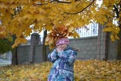 有槭树花圈的小女孩在秋天离开 库存照片