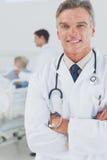 有横渡的胳膊的可爱的医生 库存图片