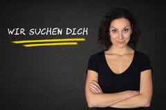 有横渡的胳膊的年轻女人和'Wir suchen在黑板背景的dich'文本 翻译:'我们正在寻找您' 皇族释放例证