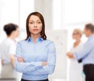 有横渡的胳膊的微笑的女实业家在办公室 库存图片