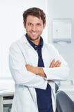 有横渡的胳膊的微笑的牙医 免版税库存照片