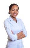 有横渡的胳膊的愉快的非洲妇女在一件蓝色衬衣 免版税图库摄影