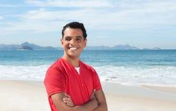 有横渡的胳膊的笑的拉丁人在海滩 免版税库存照片