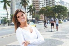 有横渡的胳膊的笑的白肤金发的妇女在城市 库存图片