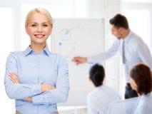 有横渡的胳膊的年轻微笑的女实业家 免版税库存图片
