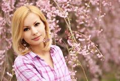 有樱花的女孩 美丽的白肤金发的妇女年轻人 免版税库存照片