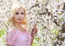 有樱花的白肤金发的女孩。春天画象。美丽的Youn 免版税图库摄影