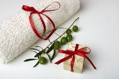 有橄榄树枝和一块毛巾的手工制造橄榄色的肥皂,作为礼物。 免版税库存图片
