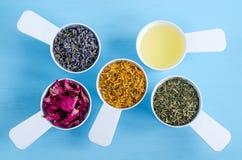 有橄榄油,干燥万寿菊、淡紫色、荷兰芹和狗玫瑰色花的塑料瓢 免版税库存照片
