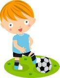 有橄榄球的一个逗人喜爱的小男孩 免版税库存照片