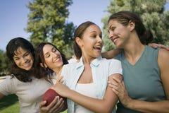 有橄榄球的愉快的妇女在公园  免版税库存照片