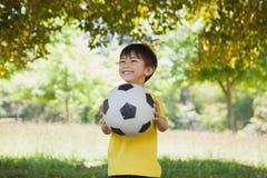 有橄榄球的愉快的逗人喜爱的小男孩在公园 免版税库存照片