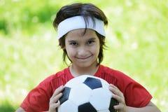 有橄榄球足球的新男孩 库存照片
