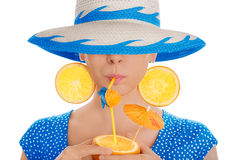 有橙味饮料和橙色佩带帽子白色背景的切片耳环的女孩 库存图片